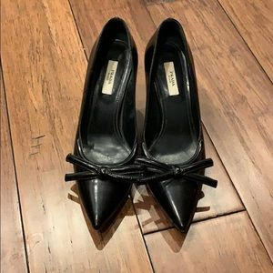 Prada black leather pumps with bow detail.